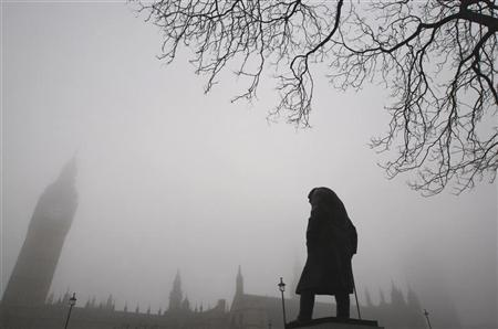 A statue of former British Prime Minister Winston Churchill is seen in front of the Houses of Parliament in morning mist at Parliament Square in central London
